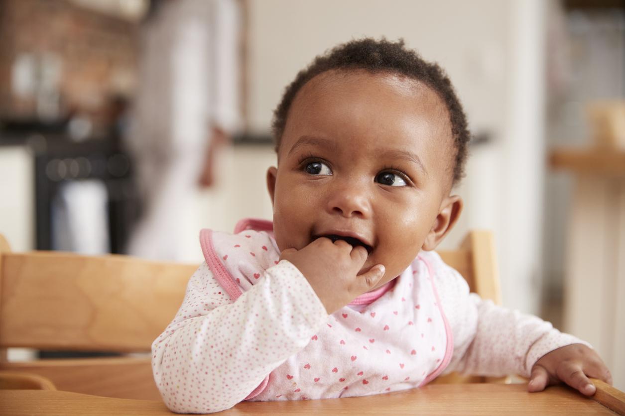 Cute Baby Girl Wearing Bib Sitting In High Chair